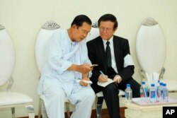 FILE - Cambodian Prime Minister Hun Sen, left, talks with dissolved main opposition Cambodia National Rescue Party leader Kem Sokha at the mourning ceremony of Sen's mother in-law, in Phnom Penh, Cambodia, Tuesday, May 5, 2020. Cambodian Prime Minister Hun Sen met Tuesday with an opposition leader whose political party was dissolved after he was charged with treason. (Pool via AP)