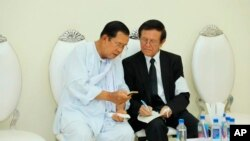 Cambodian Prime Minister Hun Sen, left, talks with dissolved main opposition Cambodia National Rescue Party leader Kem Sokha at the mourning ceremony of Sen's mother in-law, in Phnom Penh, Cambodia, Tuesday, May 5, 2020. (Pool via AP)
