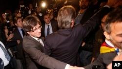 Tân chủ tịch vùng Catalonia Carles Puigdemont (trái) và chủ tịch mãn nhiệm Artur Mas (giữa, quay lưng) vẫy chào người ủng hộ trong lễ nhậm chức tại Nghị viện Catalonia ở thành phố Barcelona, Tây Ban Nha, ngày 10 tháng 1, 2016.