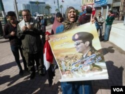"""An Egyptian woman holds a poster for the Egyptian president which reads in Arabic: """"Happy anniversary, Sisi"""" in Tahrir Square, Cairo, Egypt. Monday Jan 25, 2016. (VOA Photo/Hamada Elrasam)"""