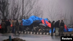 Forensic officials inspect the wreckage of a bus after a suicide bomber rammed a car into the bus carrying Central Reserve Police Force (CRPF) personnel Thursday, in Lethpora in south Kashmir's Pulwama district, Feb. 15, 2019.