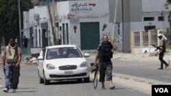 Rebeldes chequean un vehículo en un puesto de control en Trípoli.