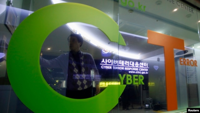 FILE - An investigator entering the Cyber Terror Response Center of the Korean National Police Agency is reflected on a window in Seoul.
