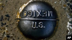 FILE - A marker embedded in the pavement marks the imaginary line between the United States and Mexico at the San Ysidro border checkpoint between San Diego, Calif., and Tijuana, Mexico, April 10, 2000.