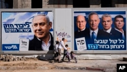 FILE - People walk by election campaign billboards showing Israeli Prime Minister Benjamin Netanyahu, left, alongside the Blue and White party leaders, from left to right, Moshe Yaalon, Benny Gantz, Yair Lapid and Gabi Ashkenazi, in Tel Aviv, Israel, April 3, 2019.