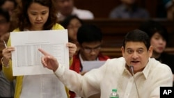 FILE - Philippine Sen. Teofisto Guingona III gestures as he shows a document during hearings into how about $81 million of Bangladesh's stolen funds were transmitted online to four private accounts at a branch of the Rizal Commercial Banking Corp. during