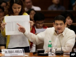 FILE - Philippine Sen. Teofisto Guingona III shows a document during hearings into how about $81 million of Bangladesh's stolen funds were transmitted online to four private accounts at a branch of the Rizal Commercial Banking Corp.