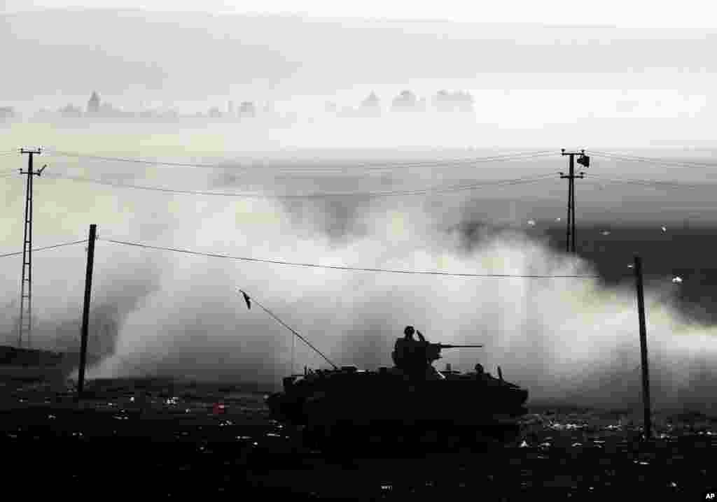 A Turkish armored vehicle patrols the border where fighting between Syrian Kurds and the Islamic State militantshas intensified, on the Turkey-Syria border, Oct. 10, 2014.