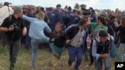 Juru kamera Hungaria Petra Laszlo (kiri tengah, berbaju biru), menendang migran muda yang baru saja menyeberangi perbatasan dari Serbia dekat Roszke, Hungaria (8/9).