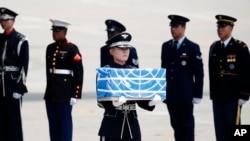 27일 한국 오산공군기지에서 군인이 북한으로부터 송환된 미군 전사자 유해가 담긴 나무상자를 운구차로 옮기고 있다.