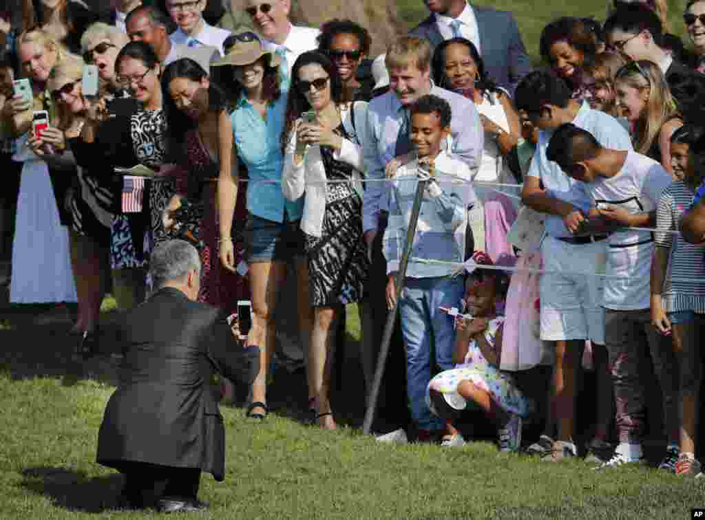 Singapore's Prime Minister Lee Hsien Loong uses his cell phone to photograph a young girl as other guests watch during a state arrival ceremony on the South Lawn of the White House in Washington.
