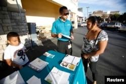FILE - Jaime Corona, patient care coordinator at AltaMed, speaks to a woman during a community outreach on Obamacare in Los Angeles, Nov. 6, 2013.
