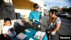 FILE - Jaime Corona, patient care coordinator at AltaMed, speaks to a woman during a community outreach on Obamacare in Los Angeles, California.