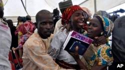 ໜຶ່ງໃນບັນດາຍິງສາວ Chibok ທີ່ຖືກປ່ອຍຕົວ ສະແດງຄວາມ ດີໃຈກັບສະມາຊິກຄອບຄົວຂອງລາວ ໃນລະຫວ່າງການໄປ ສວດມົນທີ່ໂບດແຫ່ງໜຶ່ງໃນນະຄອນຫຼວງ ອາບູຈາ, ໄນຈີເຣຍ. 16 ຕຸລາ, 2016.