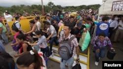People break through the barricade set up by the Venezuelan guard to travel into the Venezuelan side on the Colombian-Venezuelan border over the Simon Bolivar international bridge in San Antonio, Venezuela, April 2, 2019.