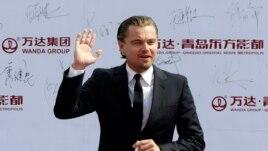 Diễn viên điện ảnh Leonardo DiCaprio chào giới truyền thông và các fan khi đến dự buổi lễ ở Thanh Đảo 22/9/13
