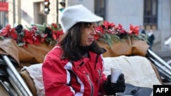Coachwoman Nathalie Matte, 52, who will lose her job when Montreal's horse-drawn carriages are taken off the roads Dec. 31, waits for passengers in Montreal, Quebec, Canada, Dec. 22, 2019. (AFP)