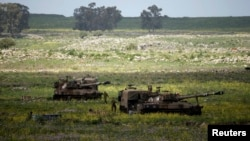 FILE- Israeli soldiers walks beside mobile artillery units near the city of Katzrin in the Golan Heights, March 19, 2014.