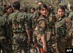 Borci Sirijskih demokratskih snaga (SDF), koje podržava Amerika, uključujući i žene, okupljaju se na proslavi u blizini naftnog polja u Omaru u istočnoj sirijskoj pokrajini Deir Ezor, 23. marta 2019, nakon proglašenja totalne eliminacije samoproklamovanog kalifata Islamske države.