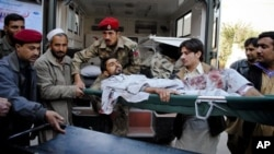 ແພດທະຫາປາກິສຖານ ແລະພວກກູ້ໄພ ສົ່ງຜູ້ເຄາະຮ້າຍຄົນນຶ່ງ ທີ່ບາດເຈັບຈາກການໂຈມຕີສະລະຊີບ ເຂົ້າໂຮງໝໍທີ່ເມືອງ Peshawar (25 ທັນວາ 2010)
