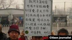 中国访民实名举牌要求周永康公布财产及维稳费 图片来源:刘修召