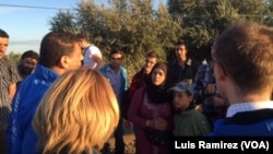 Refugees get instructions from an aid worker as they prepare to cross from Syria into Hungary.