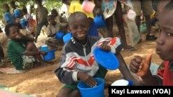 Des élèves savourant leur déjeuner à l'école primaire publique de Louanga, Togo, 23 mai 2017. (VOA/Kayi Lawson).
