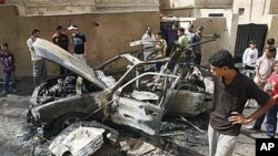 People inspect a car destroyed after a bomb attached to it exploded in Basra, Iraq's (File)