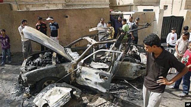 People inspect a car destroyed after a bomb attached to it exploded in Basra, Iraq's second-largest city, 550 kilometers southeast of Baghdad, Iraq, 28 Oct 2010