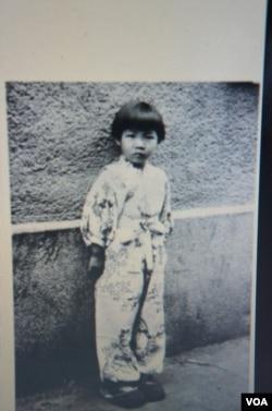 远藤向记者展示5岁时摄于长春的照片,她说这是在国共内战时期长春一场巷战之后拍摄的(美国之音歌篮拍摄)