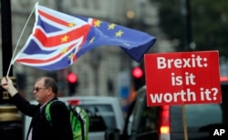 FILE - An anti-Brexit poster is seen in front of the Houses of Parliament in London, Sept. 4, 2018.