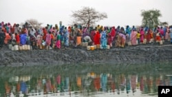 Displaced women gather to collect water from a water hole near Jamam refugee camp in South Sudan's Upper Nile State, March 10, 2012.