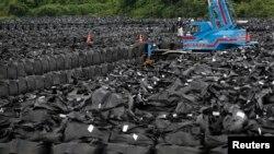 Trabajadores remueven tierra contaminada en el pueblo de Naraha, cerca de la planta nuclear de Fukushima, dañana en el terremoto de 2011.