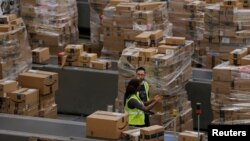 Workers walk past boxes to be shipped inside of an Amazon fulfillment center in Robbinsville, New Jersey, Nov. 27, 2017.