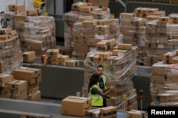 FILE - Workers walk past boxes to be shipped inside of an Amazon fulfillment center in Robbinsville, New Jersey, Nov. 27, 2017.