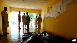 Des membres de la famille attendent de réclamer les corps des victimes d'un attentat-suicide dans un hôpital de Konduga, près de Maiduguri, au Nigéria, le 16 août 2017.