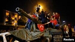 People stand on a Turkish army tank in Ankara, Turkey, July 16, 2016.