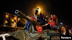 Warga berdiri di atas tank angkatan darat Turki di Ankara (16/7). (Reuters/Tumay Berkin)