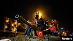 People stand on a Turkish army tank in Ankara, Turkey, July 16, 2016.