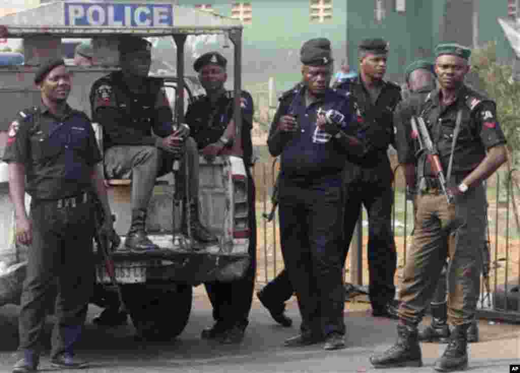 Policemen stand guard as angry youths protest on day five of the nationwide strike following the removal of a fuel subsidy by the government, in Lagos, Nigeria, Friday, Jan. 13, 2012. Unions in Nigeria announced Friday a weekend pause in a paralyzing nati