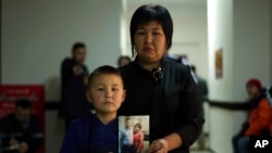 In this Dec. 7, 2018, photo, Sala Jimobai stands with her son, Aqzhol Dakey, holding a picture of her husband Dakey Zhunishan for a photo outside the office of an advocacy group for ethnic Kazakhs born in China in Almaty, Kazakhstan.