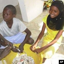 Students tear paper before making paper briquettes, Diourbel, Senegal, December 5, 2011.