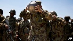 An Afghan Army soldier adjusts his helmet at a training facility near Kabul, May 8, 2013 (AP Photo/Anja Niedringhaus, File) May 8, 2013