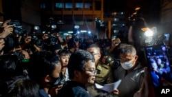 Aktivis pro-demokrasi dan pengacara hak asasi manusia Arnon Nampha, tengah, di kantor polisi setelah unjuk rasa di Monumen Demokrasi di Bangkok, Thailand. (Foto: AP)