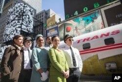"""Para aktor mengenakan busana pilot, awak kabin, dan mekanik dari tahun 1960an dan 70an. Mereka berpose di samping Lockheed Constellation L-1649A Starliner, atau dikenal dengna nama """"Connie, yang parkir di Times Square di New York, untuk acara promosi, Sabtu, 23 Maret 2019."""
