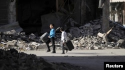 Trẻ em đi bộ trên đường phố hoang tàn ở Deir al-Zor miền đông Syria, 6/2/14