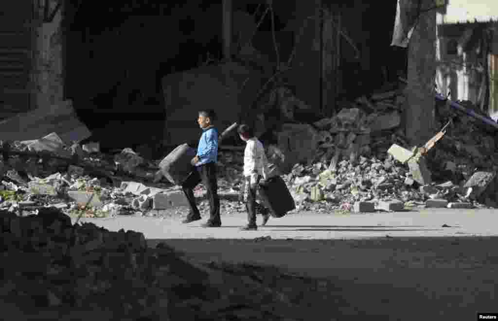 Boys walk along a damaged street in Deir al-Zor, eastern Syria, Feb. 6, 2014.