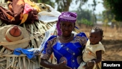 FILE - A woman carries her child in Nigeria's Kaduna State.