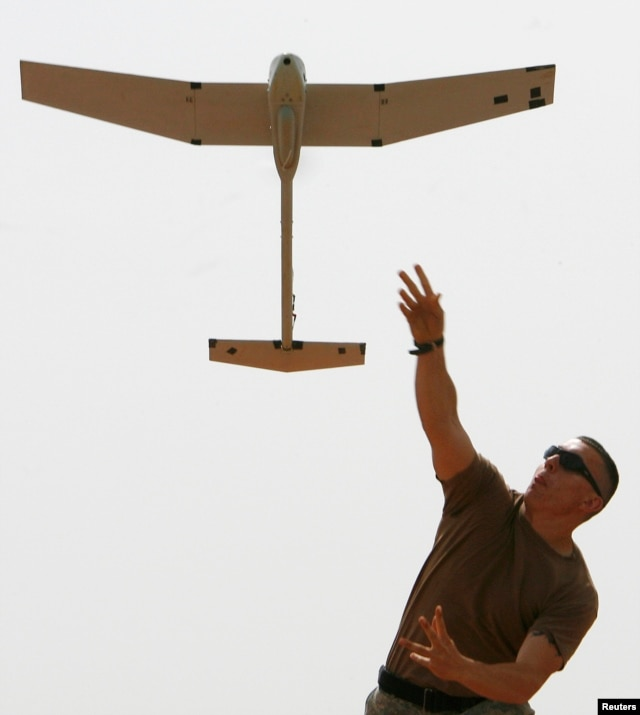 FILE - A soldier with the U.S. Army's 10th Mountain Division launches a remote controlled Raven observation drone from a military base in Mahmudiya, south of Baghdad, April 28, 2007.
