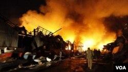 Seorang warga memeriksa lokasi pasca ledakan dini hari gudang obat di Yangon (Rangun), Burma (29/12).